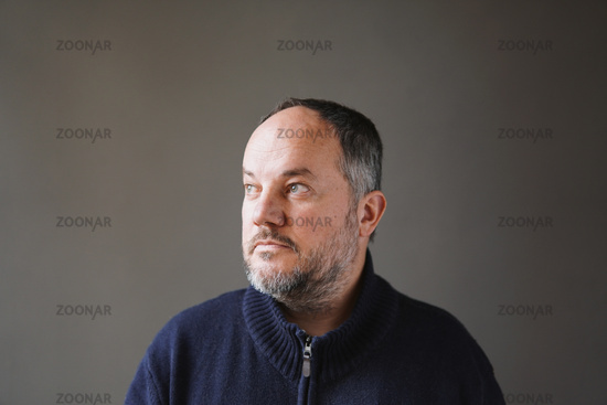 50 year old man with graying hair and beard looking away thinking