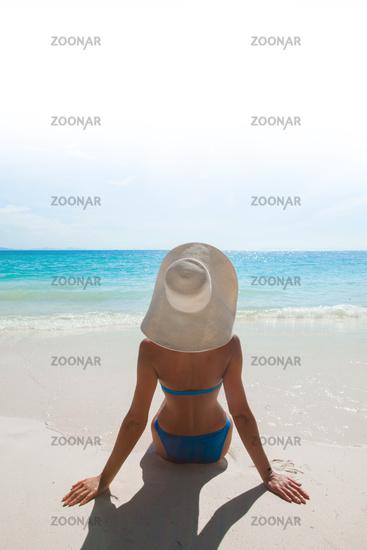 Woman in sunhat on sea beach