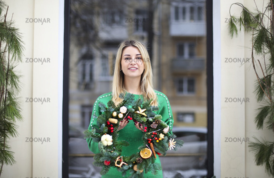 Girl holding Christmas wreath maked by herself