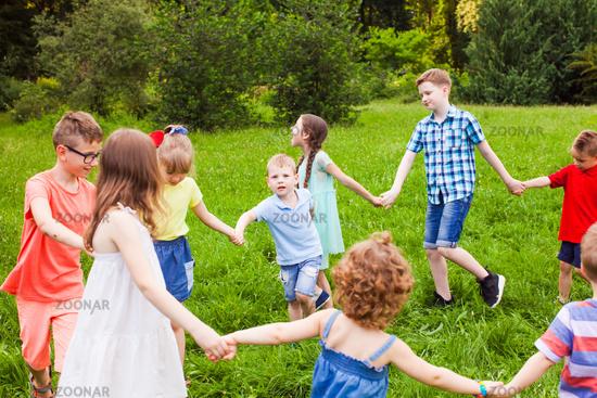 Cute little children doing circle dance outdoors