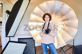 Fotografin mit Kamera und Studioleuchten