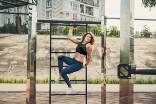 Attractive fit young woman in sport wear rest on the street workout area. The healthy lifestyle in the city. Street portrait strong woman poses at gym. Beautiful athletic woman in sports bra posing