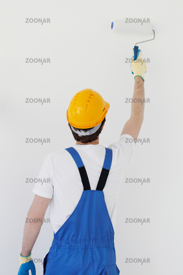 Worker painting walls in new house