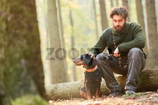 Revierförster sitzt mit einer Bracke im Wald