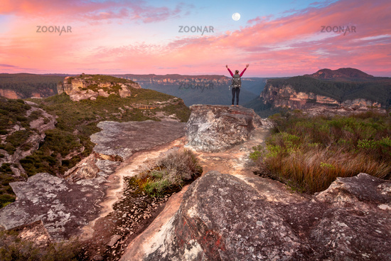 Woman standing on summit rock ledge views of sunrise valley