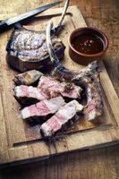 Barbecue dry aged tomahawk pork steak sliced as top view on an old rustic board with hot barbecue sauce