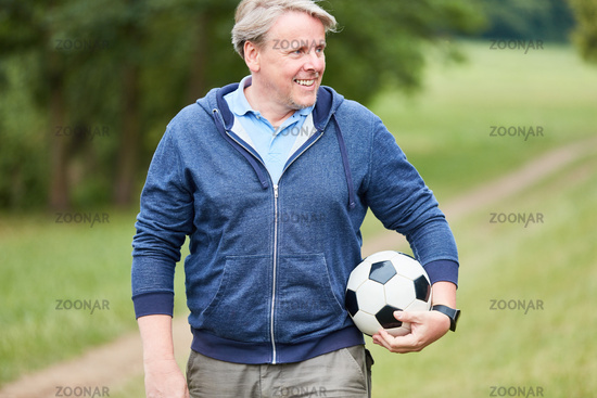 Trainer mit einem Fußball in der Natur