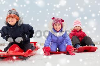 happy little kids sliding down on sleds in winter