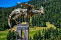 Bronze dragon statue on pole, mountain landscape, forest and alpine pasture