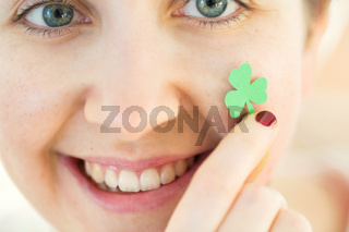 close up of happy young woman face with shamrock