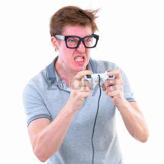 Funny young nerd man with big eyeglasses playing games and looking angry