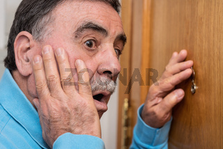 Senior man looking through peephole