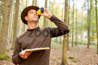 Förster bestimmt die Baumhöhe im Wald