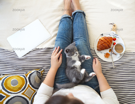 Young woman with cute little kitten sitting on bed at home having breakfast and using laptop