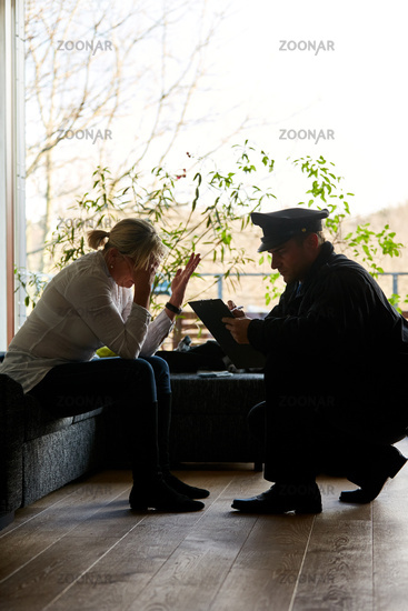 Frau redet mit Polizist nach Einbruch