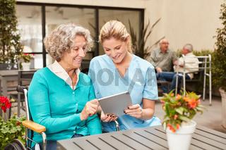 Seniorin und Pflegekraft mit einem Tablet PC