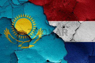 flags of Kazakhstan and Netherlands painted on cracked wall