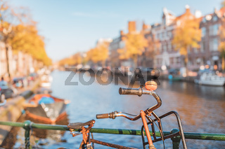 Bicycle with orange bell in front of canal in Amsterdam in autumn