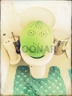 green balloon with painted face on a toilet