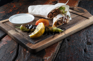 Turkish and Arabic traditional Ramadan Adana kebab roll wrap serving with yogurt and hot pepper on rustic wooden background