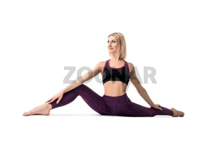 Slim blonde in a split doing yoga isolated view