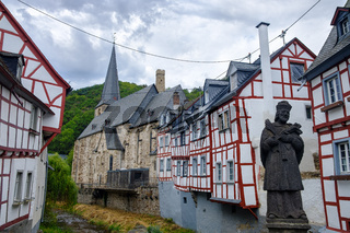 The picturesque village of Monreal with John of Pomuk Statue at the stone bridge in Eifel region, Germany