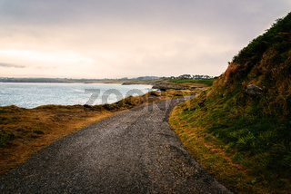 Scenic view of lonely road by the sea against cloudy sky