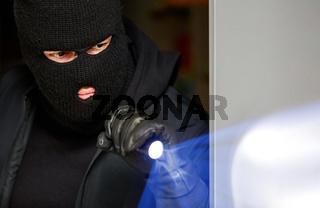 Einbrecher im Haus nachts mit Taschenlampe