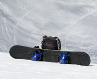 Snowboard and black backpack on snow in high winter mountains