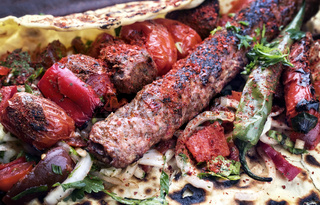 Traditional Adana Kebap with tomato and salad on a flatbread as close up