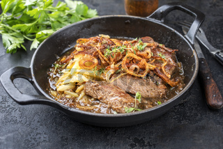 Traditional dry aged sliced roast beef with fried onion rings and Swiss rosti as top view in a cast-iron skillet with brown sauce