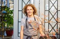 Junger Mann als Florist in seinem Blumenladen