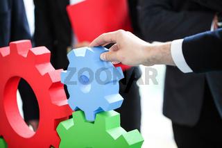 Business people assembling cogwheels