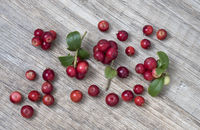 Lingonberry (fruits of Vaccinium vitis-idaea) with leaves, on wooden background, top view.