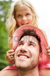 Glücklicher Vater trägt Tochter huckepack