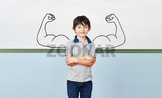 Schüler in Grundschule mit Muskeln vor Whiteboard