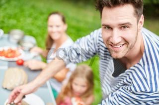 Mann und Familie beim Frühstück im Garten