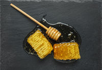 honeycomb and honey stick on a black