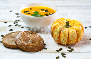 organic pumpkin soup in a white bowl framed by pumpkin and chestnut bread and pumpkin seeds