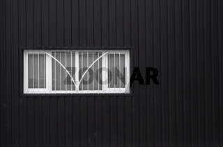 Black and white Corrugated metal sheet texture surface on a building wall with windows. Galvanize steel background.