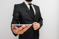 Male human with beard wear formal working clothes hold high technology smartphone device. Man dressed in work suit plus tie holding small mobile hi tech phone using one hand