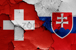 flags of Switzerland and Slovakia painted on cracked wall
