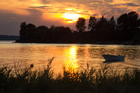 Brilliant sunset after thdunderstorm at the lake with boat in Scandinavia, Denmark