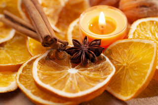 Orange slices, spices and candle as Christmas decoration