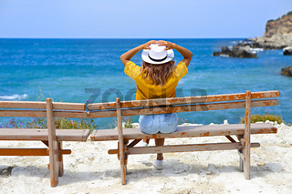 Pretty young woman in a straw hat sitting on a bench in front of the sea