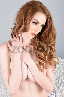 Ashley Foxx, sexy, vollbusige Rothaarige, Oben Ohne, sitzt auf einem Kissen