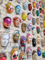 Moscow, Russia, 21 October 2019: Colorful painted ceramic faces sculpture on the bricks wall as an the object of modern art. Hundred faces by Marat Nabi. Bricks wall with decorative element