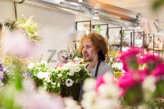 Florist zwischen bunten Schnittblumen im Blumenladen