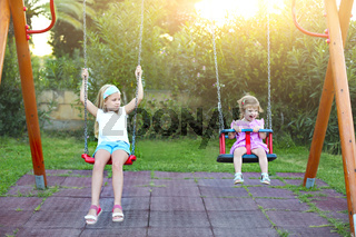 Two little sisters on the swing