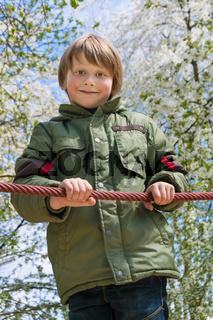 Cheerful blond boy at playground